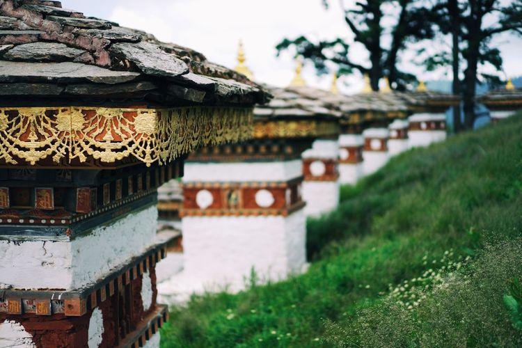 Row of stupas on grassy field