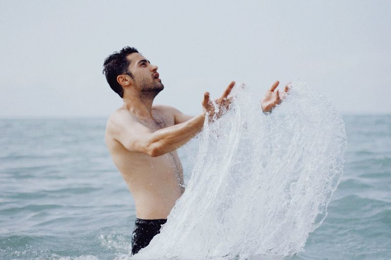 Splash Water Shirtless Men Sea Leisure Activity Three Quarter Length Nature Beach Waist Up Day Outdoors Young Men Arms Raised