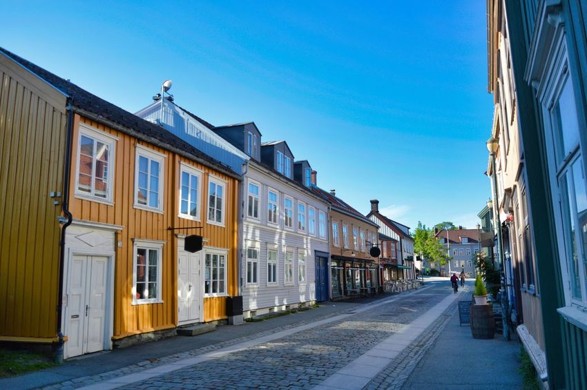Street view from Trondheim, showing typical architecture and cobbled street. Cobblestone Streets Commercial Street Norway Scandinavia Street View Trondheim Architecture Blue Blue Sky Building Exterior Built Structure Clear Sky Cobblestone Day Daylight Grey Color Historic Norwegian Outdoors Shadows Sky Summer Typical Building Window Yellow Color