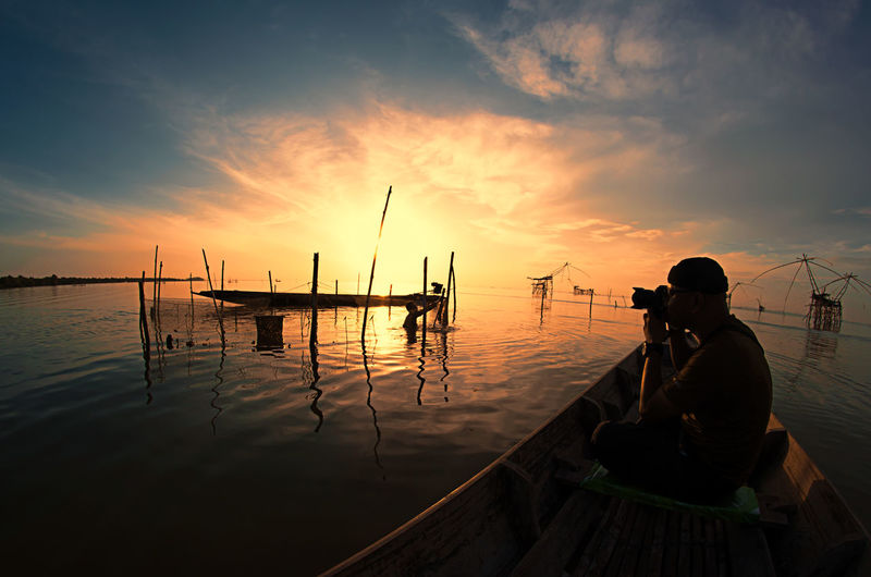 Man photographing sea while sitting in boat against sky