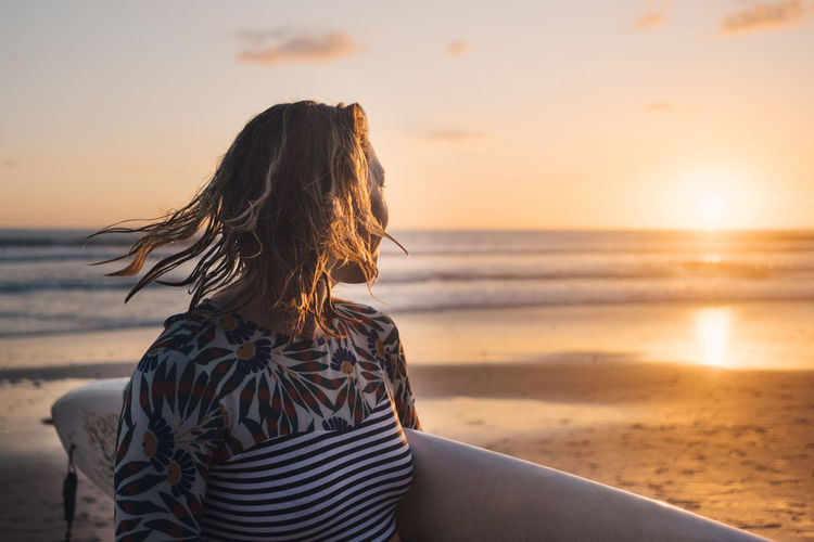 Rear view of woman looking at sea shore during sunset