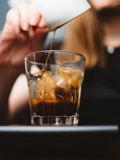 Midsection of woman pouring coffee in glass on table