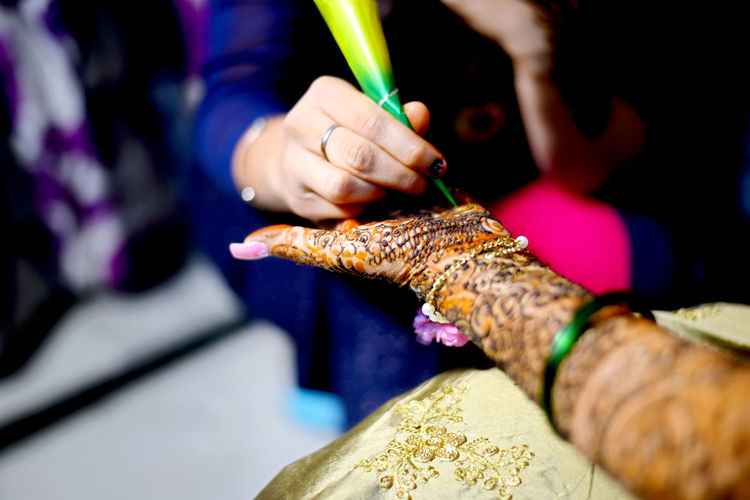 Midsection of woman making henna tattoo on friend palm