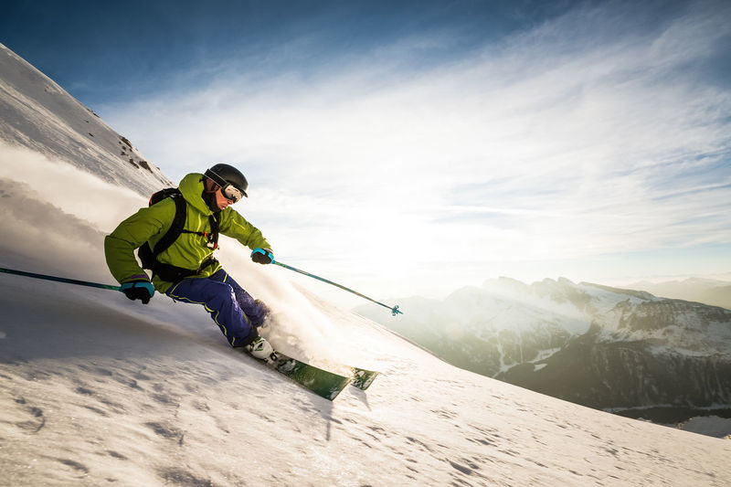 Man skiing on snowcapped mountains against sky