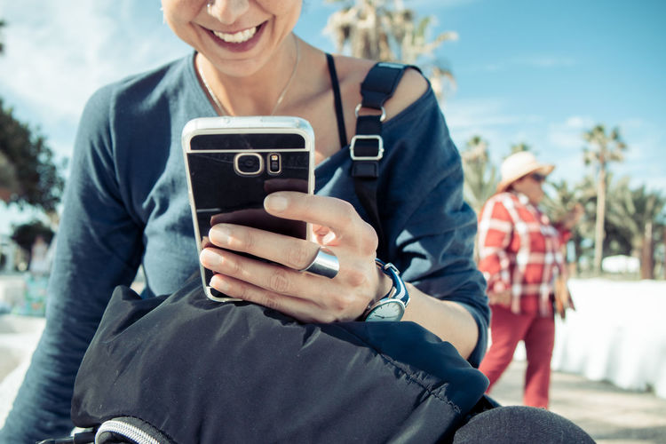 Midsection of woman using mobile phone while sitting outdoors