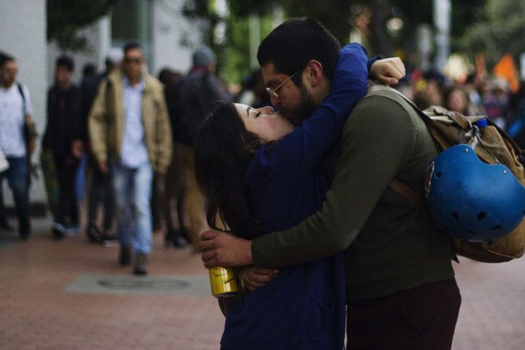 Young couple kissing while standing on street