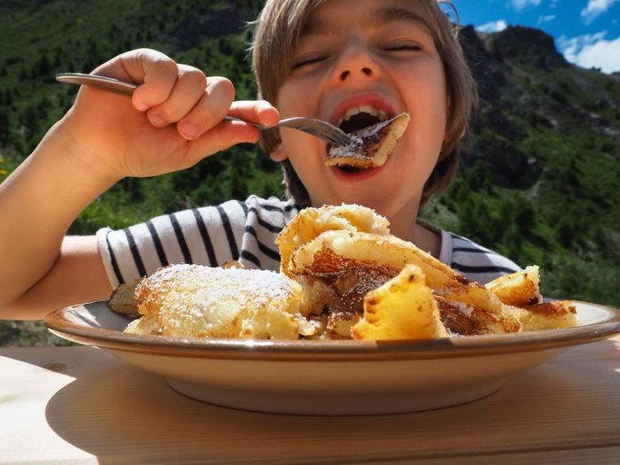 Boy eating dessert from plate