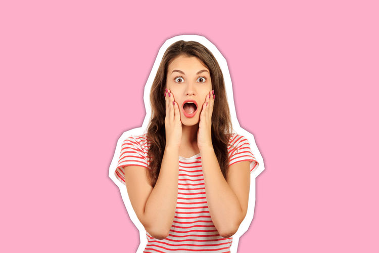Portrait of young woman standing against pink background