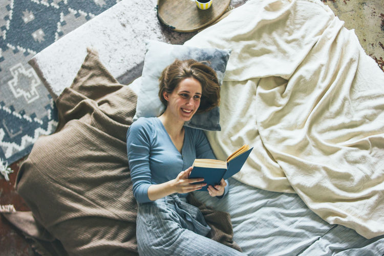 Woman holding a while sitting on bed