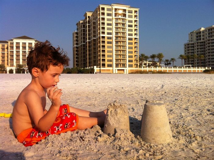Shirtless boy looking at sand in city