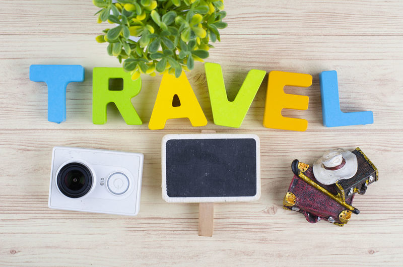 top view vacation and holiday concept word TRAVEL with accessories on wooden background Wood - Material Indoors  Table Directly Above Communication No People Text Still Life Western Script Creativity Education Capital Letter Multi Colored Arrangement High Angle View Flower Plant Close-up Learning Medium Group Of Objects