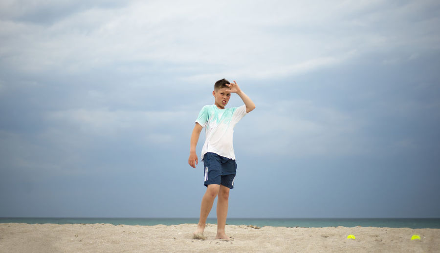 The boy trains on the sand by the sea. general physical preparation. tennis player.