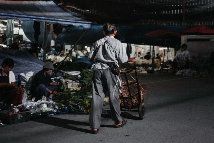 Man pushing cart on road in city at night