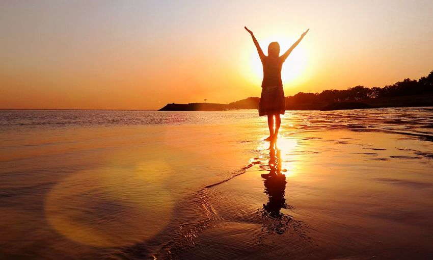 Silhouette woman with arms raised standing at beach during sunset