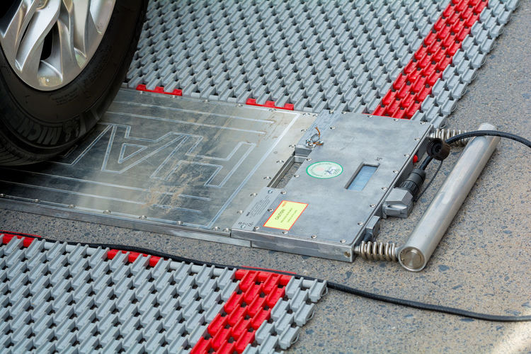 Police set up portable wheel load scales for determining the weight of heavy vehicles on the road for law enforcement and could reduce roads accidents . Close-up Day Indoors  Industry Law Enforcement Machine Part Machinery Manufacturing Equipment No People Portable Wheel Load Scales Red Technology Transportation