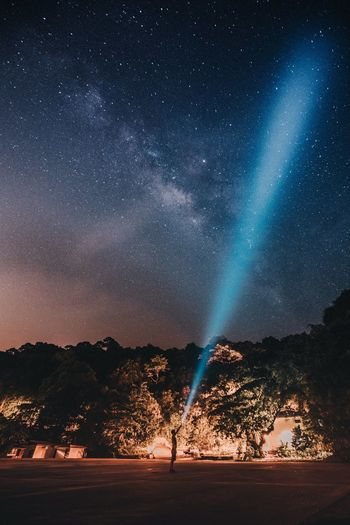 Man Standing By Mountain With Flashlight Towards Star Field At Night
