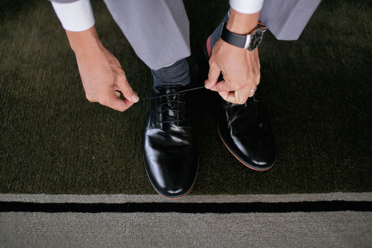 Man's hands tying shoelace of his new shoes. Shinny Adult Black Color Businessman Close-up Day High Angle View Human Body Part Human Hand Human Leg Low Section Men Only Men People Real People Shoe Well-dressed Fresh on Market 2017 Be. Ready. Business Stories