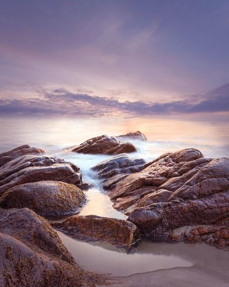 Rock formations at sea shore against sky during sunset