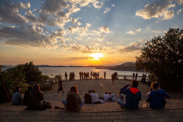 People looking at view of sunset