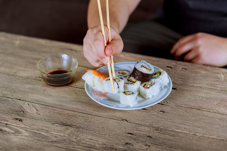 Cropped hands of child eating sushi on wooden table