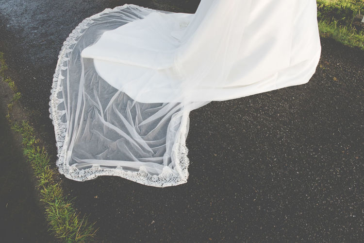 Low section of bride wearing wedding dress on road
