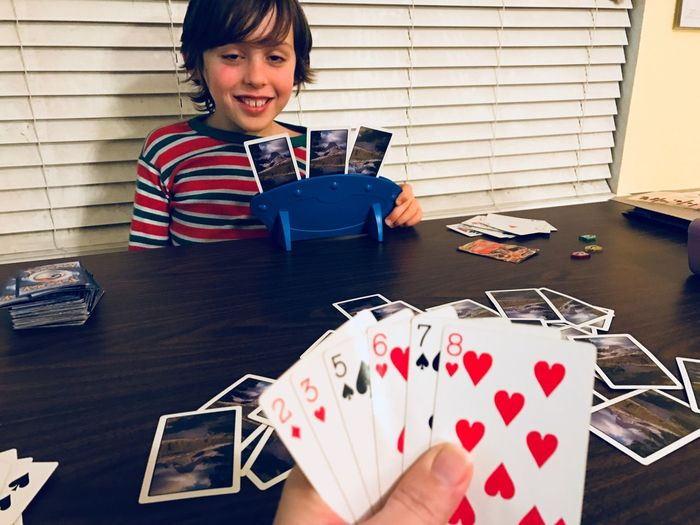 Lifestyles Leisure Child Boy Hanging Out Quality Time Sitting Family Fun Table One Person Cards Indoors  Playing Holding Leisure Games People Smiling Human Hand