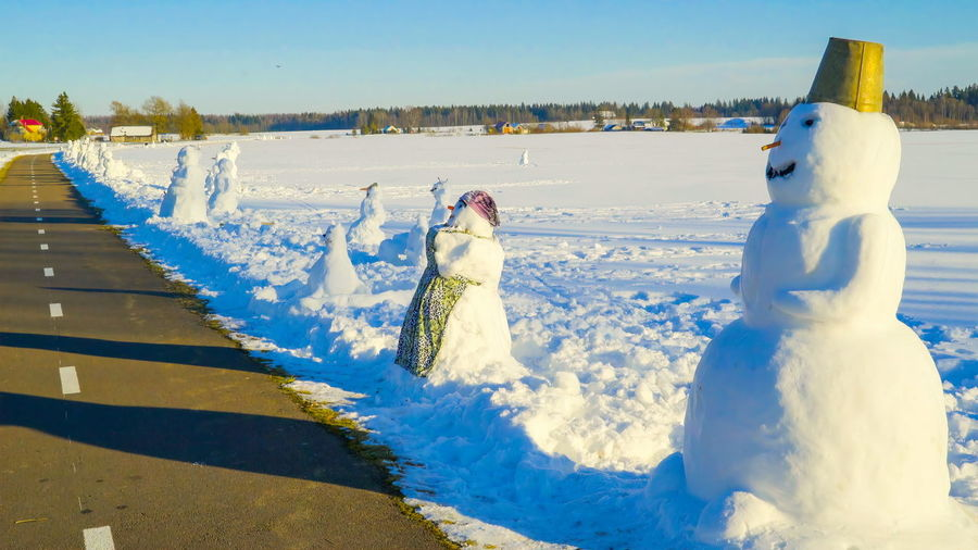 One of the many snowman on the roadside on the big wide field filled with snow Cold Temperature Snow Winter Nature Sky Representation No People Snowman Creativity Day Art And Craft White Color Human Representation Sunlight Bird Sculpture Blue Outdoors Landscapes Cold Temperature Snowing Nature Climate Polar Climate Village Seasons Ice Scenics Travel Weather Winter Fun