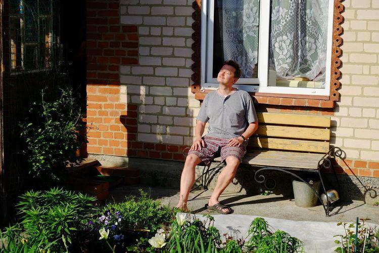 Full length of man sitting on seat in yard