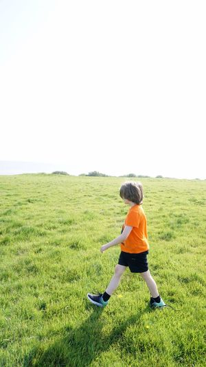 Full length of boy walking on grass against clear sky