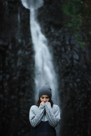 Portrait of young woman standing against waterfall