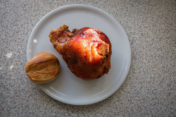High angle view of fried chicken with bread in plate on marble