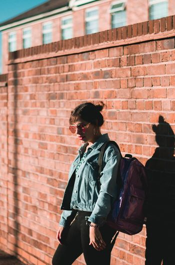 Young Woman Carrying Backpack While Standing By Brick Wall