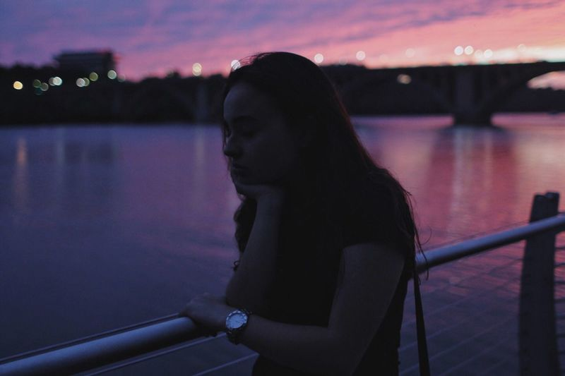 Thoughtful Woman Standing By Railing And River During Dusk