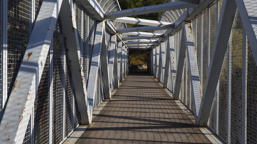 Empty bridge amidst buildings