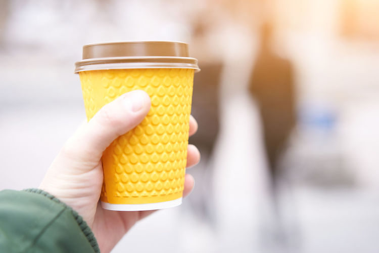 Close-up of hand holding yellow juice
