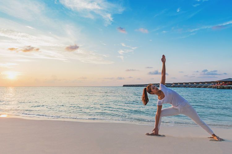 Asian woman wearing white sportswear practicing yoga Triangle pose or Utthita Trikonasana pose on the beach in Maldives at sunset,Feeling so comfortable and relax in holiday,Healthy Concept Sea Water Sky Beach Lifestyles Land Leisure Activity Exercising One Person Beauty In Nature Real People Full Length Healthy Lifestyle Horizon Over Water Stretching Relaxation Exercise Yoga Sport Horizon Outdoors Human Arm Handstand  Arms Raised Activity Angle Asana Ashtanga Asian  Athletic Attractive Balance Beauty Body Part Calm Concentration Energy Exercise Extended Fitness Happiness Harmony Healthy Lifestyle Maldives Meditation Palm Paradise Pose Practice Pretty