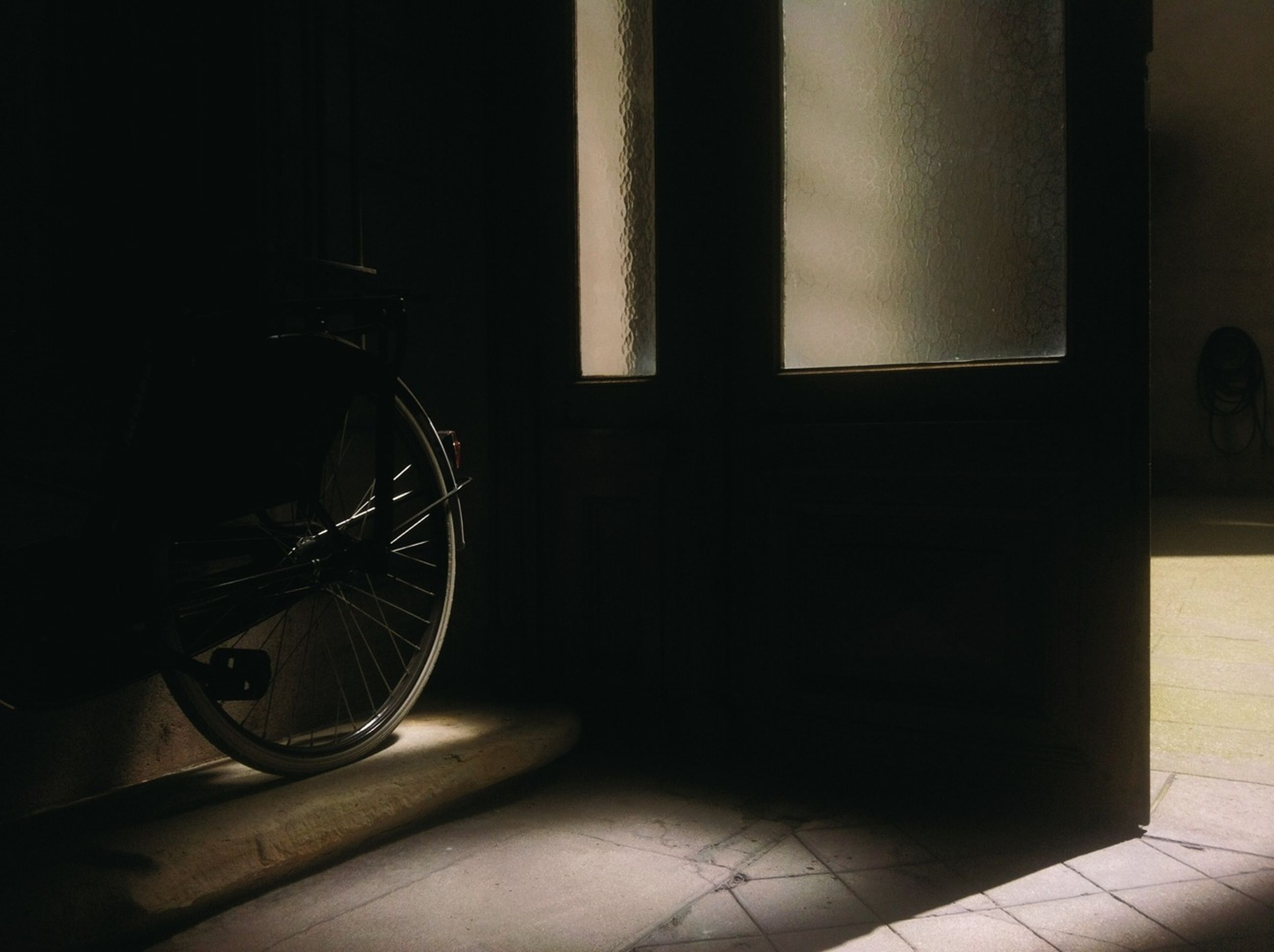 indoors, window, home interior, door, architecture, built structure, absence, no people, table, flooring, tiled floor, empty, sunlight, glass - material, chair, house, wall - building feature, day, bicycle, shadow