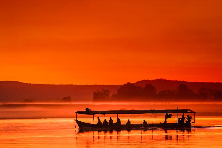 Silhouette boat in sea against orange sky