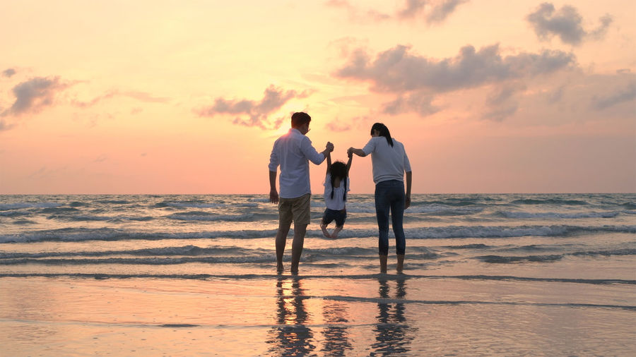 Friends standing on beach against sky during sunset