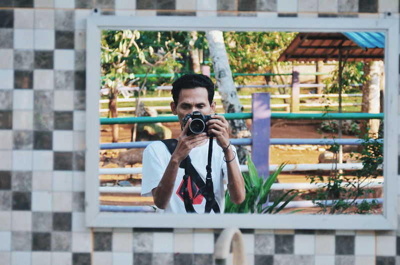Reflection Of Man Photographing In Mirror