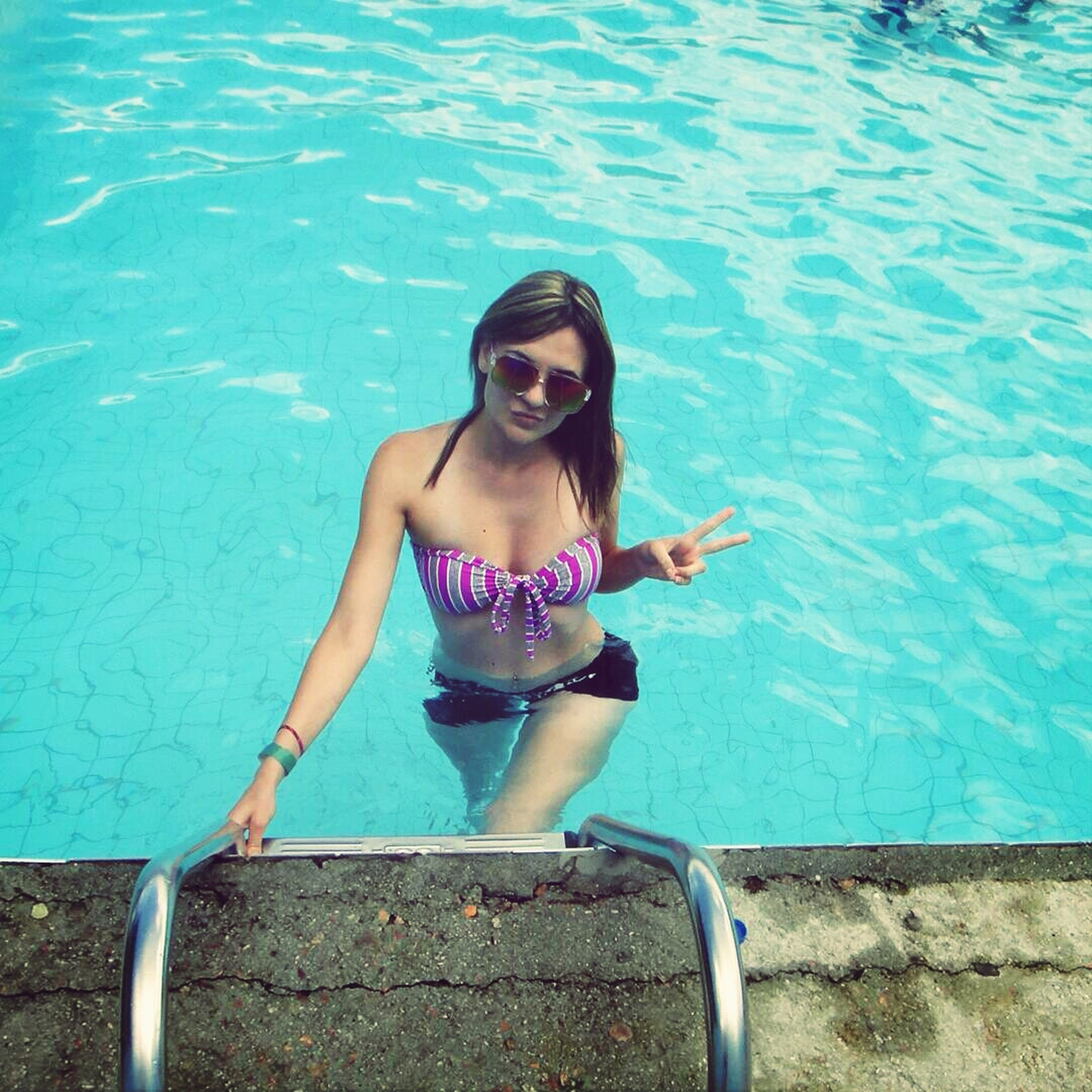 water, lifestyles, person, leisure activity, young adult, casual clothing, portrait, young women, looking at camera, blue, standing, swimming pool, front view, high angle view, full length, smiling, sunglasses