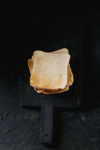 Srack of Fresh toasts bread on black wooden cutting board over black textured background. Top view Breakfast Toast Black Background Bread Cutting Board Flat Lay Food Food And Drink Healthy Eating Ready-to-eat Table Toasted Bread Top View Of Food White Bread Wood - Material