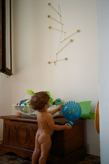 Rear view of shirtless boy standing against wall at home