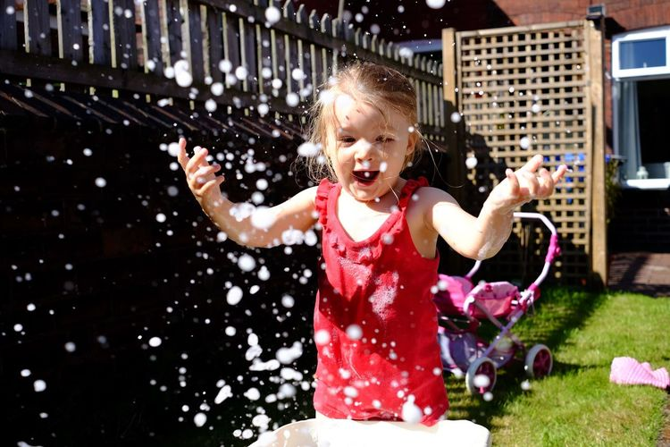 Portrait Of Happy Girl Playing In Water