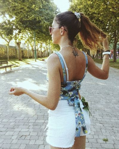 Rear view of woman with arms raised standing against tree
