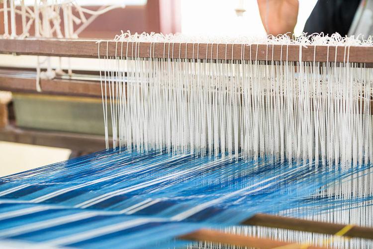 Worker weaving loom in factory