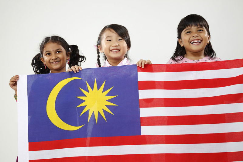 malaysian multi racial kids holding flag together Celebration Happiness Indian Innocence National Day Patriotism Traditional Clothing Child Childhood Chinese Emotion Flag Front View Group Of People Harmony Looking At Camera Malay Ethnicity Malaysia Malaysian Multi Racial Pride Smiling Togetherness White Background Women