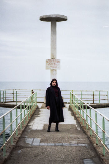 Portrait Of Young Woman Standing On Pier Over Sea Against Cloudy Sky