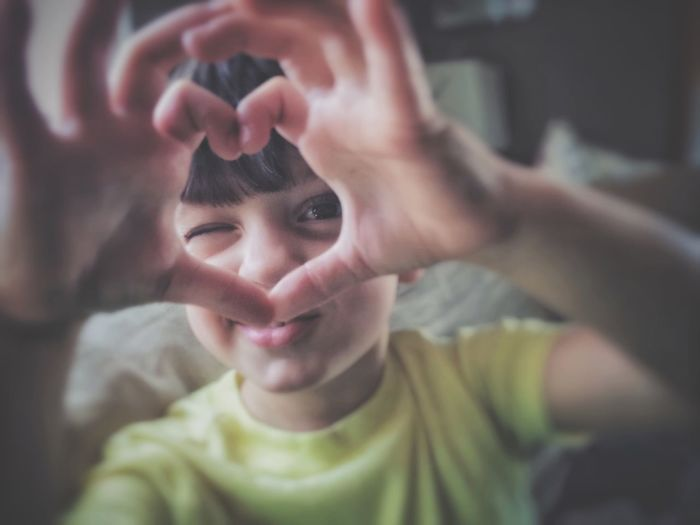 Portrait Of Boy Making Heart Shape With Hands