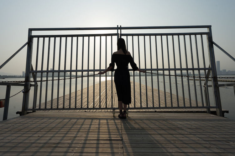 Rear view of silhouette woman standing on railing against sea